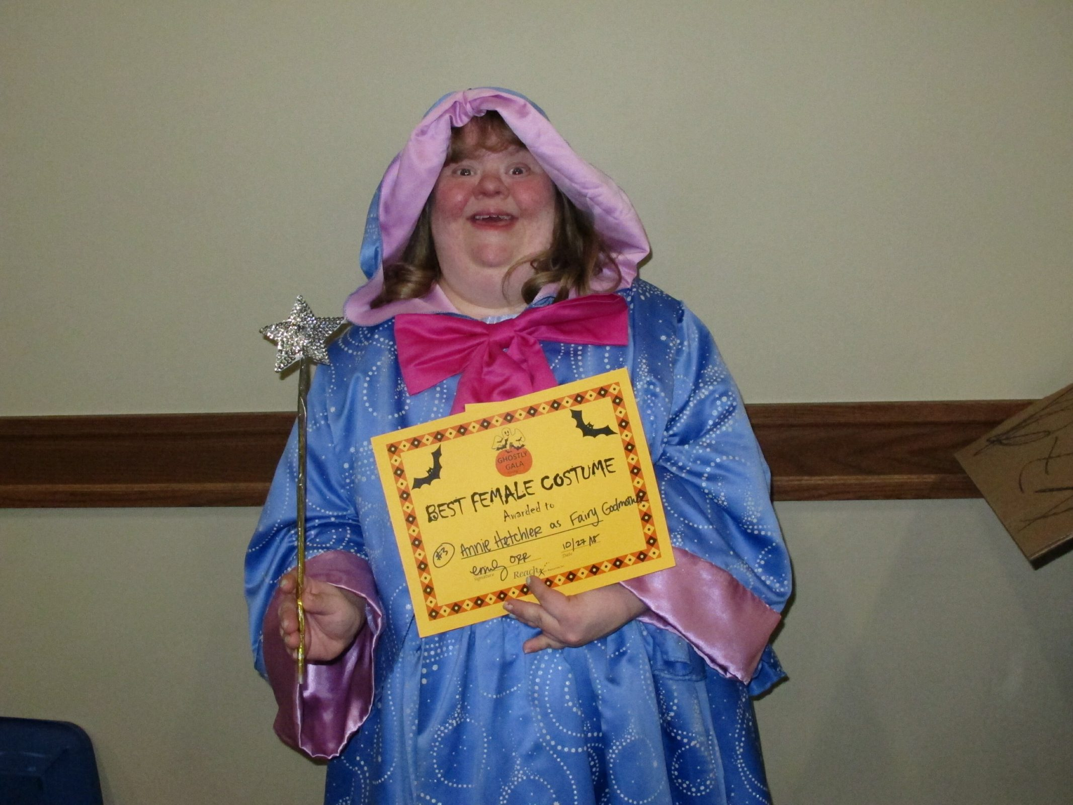 Young woman wearing Fairy Godmother costume smiles and holds her certificate for the best female costume for the Ghostly Gala