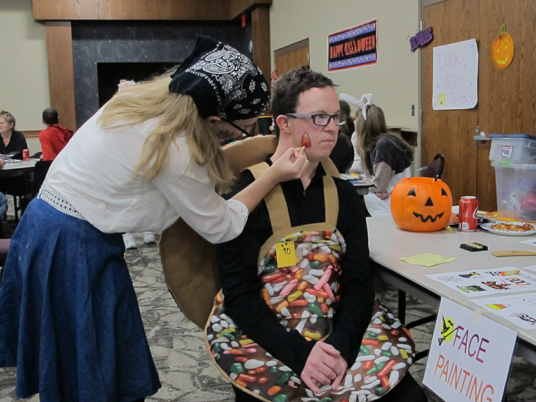 Young man wearing a candy bowl costume sits at a face painting station while a teenage girl paints on his cheek