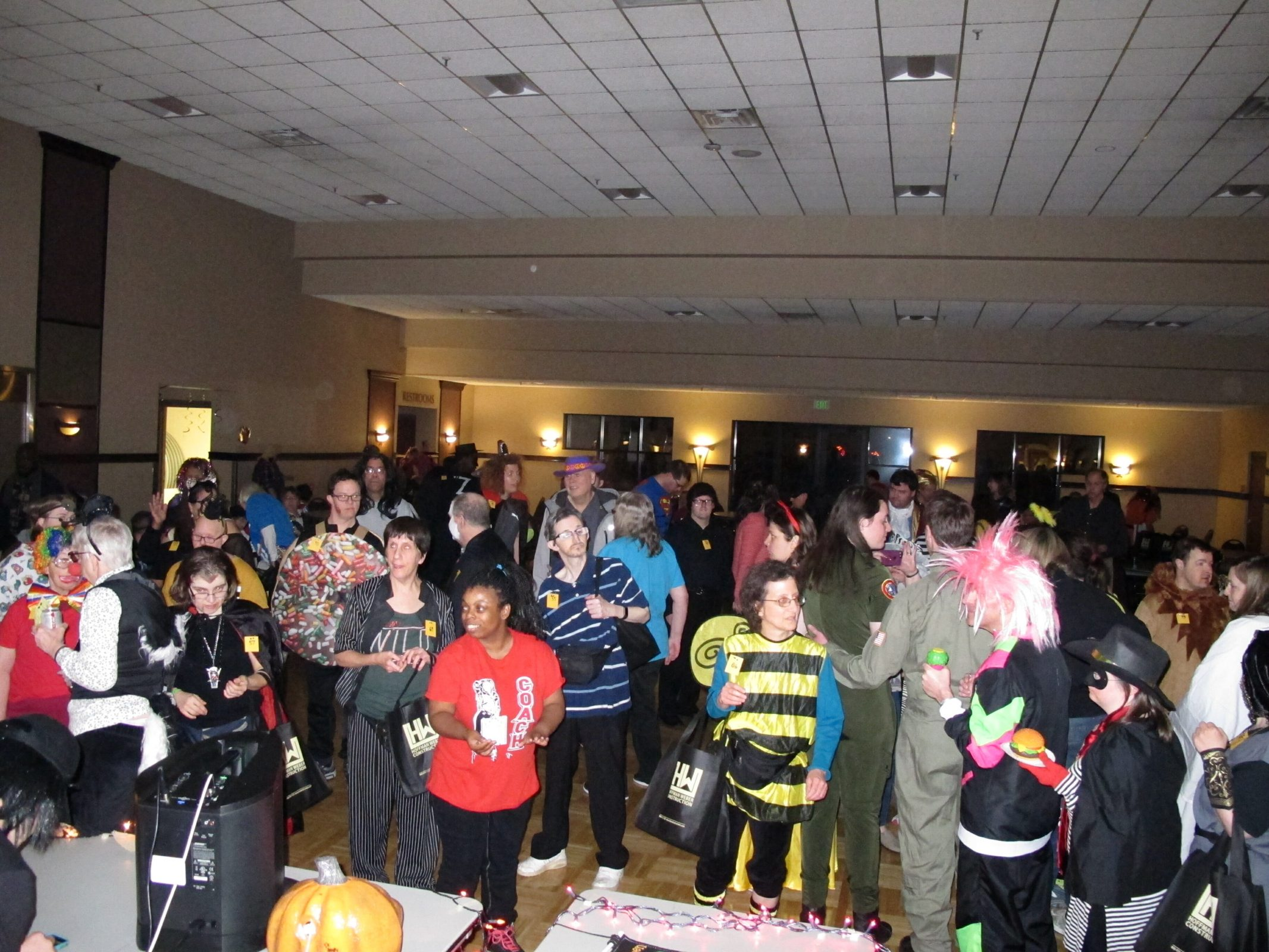 A large diverse group of people in Halloween costumes dancing in dim room