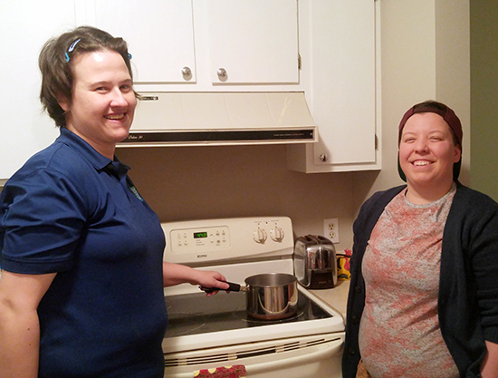 Two young women stand at stove with saucepan
