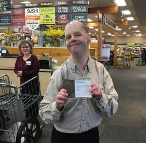 Male employee holding certificate at grocery store