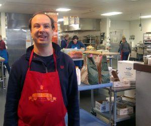 man wearing apron at food kitchen
