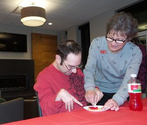 woman helping man decorate cookie