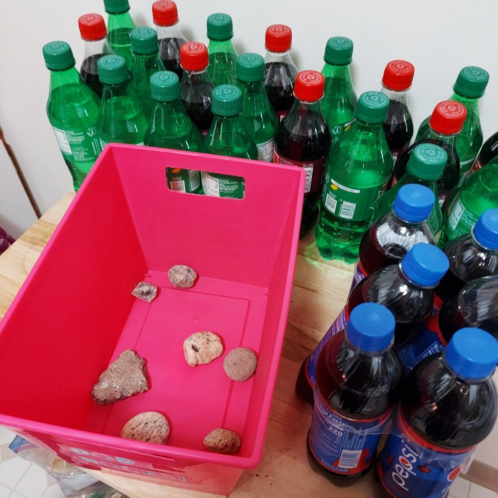 Pop rocks with rocks in bin and soda around it.