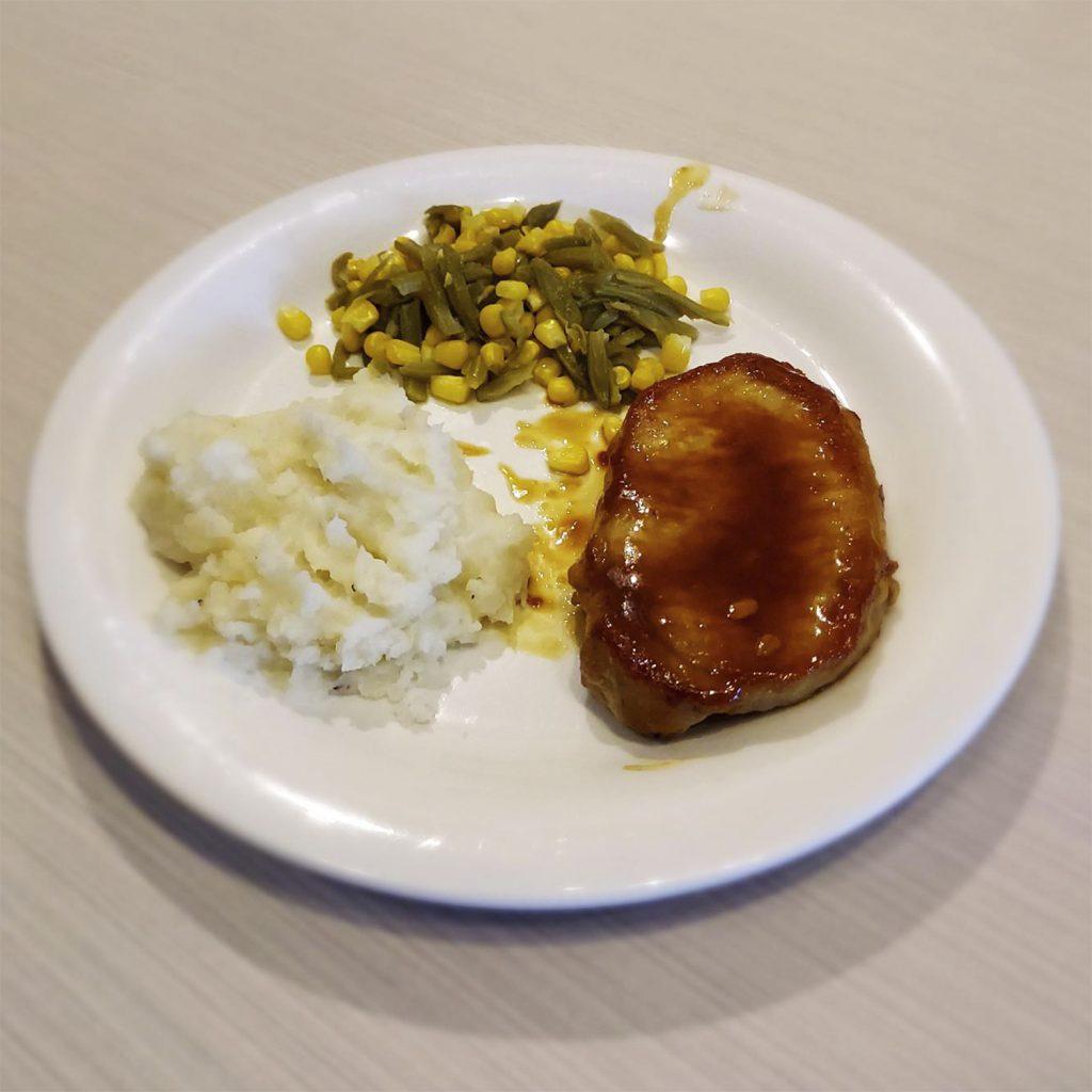 Calli's pork chop meal with mash potatoes and veggies.