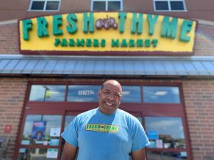 Andrew in a blue shirt standing in front of Fresh Thyme Store.